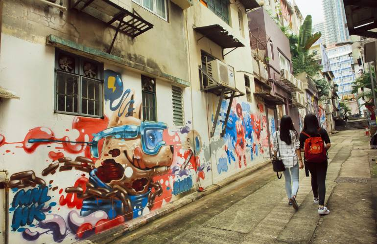 Two women walking at narrow street with street art in big city