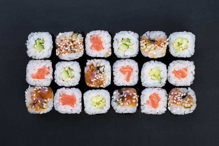 Mix of Japanese nori rolls on a black background