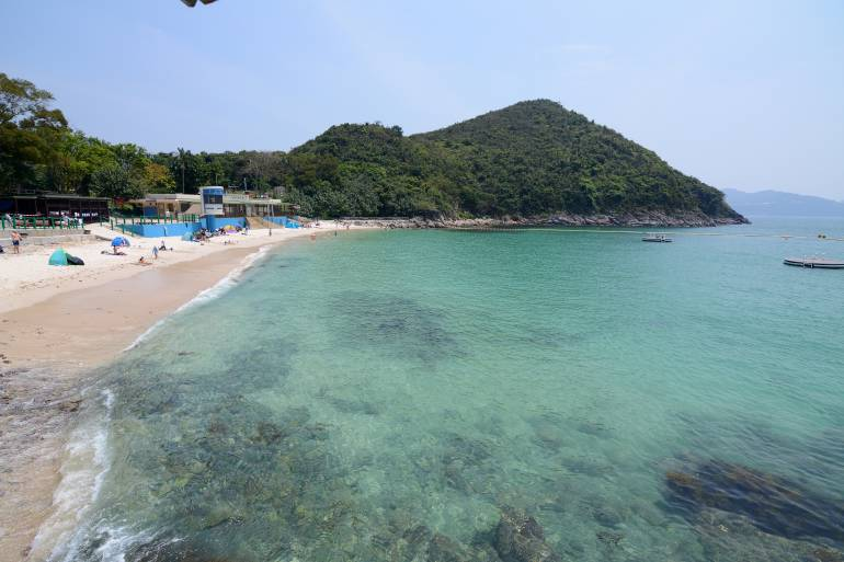 People sunbathing at idyllic Hap Mun bay, Sharp island, the largest island in the Kiu Tsui Country Park located at Port Shelter of Sai Kung, Hong Kong. Sharp Island is under the administration of Sai Kung District