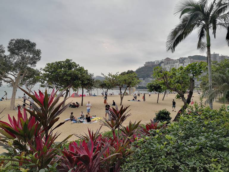 People realx at Repulse Bay beach, Hong Kong island South coastline busier tourist spot.