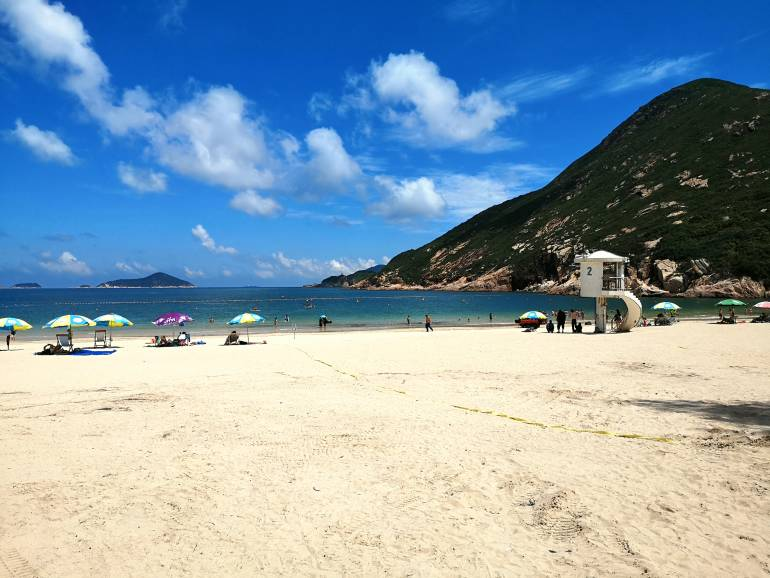 People sunbathing at Shek O Beach, a sandy public beach at Shek O village, a popular weekend and holiday destination located on Hong Kong southern coast.