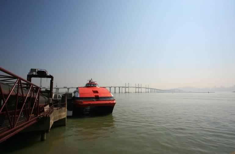 The Hong Kong Macau Ferry in Macau harbour with the Hong Kong Zhuhai Macao Bridge in the background.