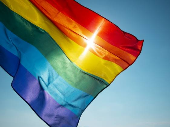 rainbow flag waving on the blue sky