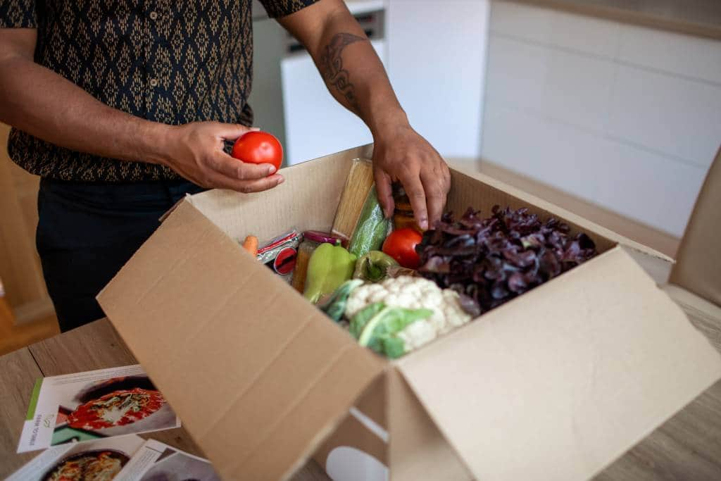 man opening box of groceries