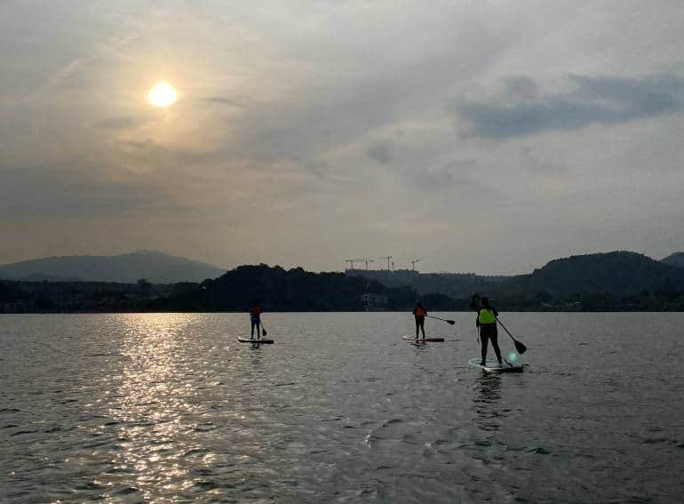 Three people on stand-up paddle boards in Hong Kong