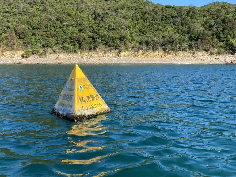 Do Not Moor buoy in the water with island greenery in the background