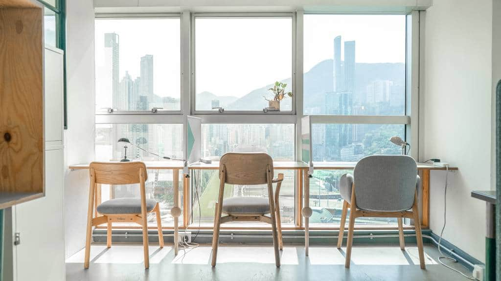 Three desks in coworking space in front of window overlooking the city below