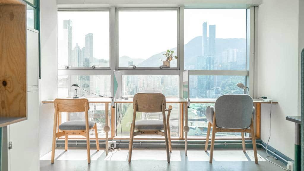 Three desks in coworking space in front of window overlooking the city below
